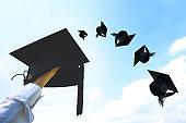 Graduation day, Images of hand holding Caps or hat throwing in the air with sunshine day on blue sky background, Happiness feeling, Commencement day, Congratulation, Ceremony