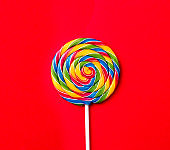 Tasty appetizing Party Accessory Sweet Treat Swirl Candy Lollypop on Bright Red Background Top View Minimalism Fashion Conceptual