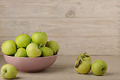 Green apples in a lilac plate on a wooden light background.