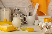 Kitchen utensils, tools and products for homemade cakes on a light wooden background.