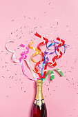 Champagne bottle with colorful party streamers on pink background.