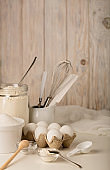 Kitchen utensils and tools for homemade baking on a light wooden background.