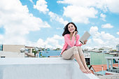 Asian young woman relaxing under blue sky on rooftop