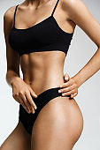 Sporty woman in black lingerie cares about her body