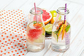 Infused flavored water with fresh fruits on white wooden background. Refreshing summer homemade detox water