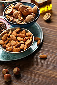 Almond nuts and walnuts in bowls, food closeup