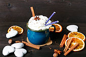Christmas coffee cup with whipped cream, cinnamon, cocoa powder, anise, dried orange ang gingerbread cookies on wooden table. Dark retro style with copy space.