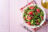 Fresh salad with arugula, grapefruit, avocado, pomegranate seeds and pine nuts.