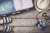 Travel preparations concept with suitcase, clothes and accessories on an old wooden table.