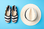 Straw hat and espadrilles on blue background