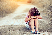 Lonely and sad little girl sitting in the park in vintage color tone