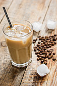 cold coffee glass with ice cubes on wooden table background