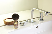 Shaving brush, traditional safety razor, shaving soap, set next to a designer wash basin