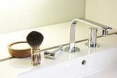 Shaving brush, traditional safety razor, shaving soap, set next to a designer wash basin