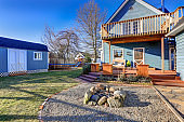 Exterior of blue craftsman house with covered back porch, fire pit and playset.