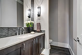 White and brown bathroom boasts a nook filled with taupe vanity