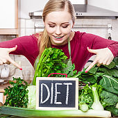 Woman in kitchen having green diet vegetables
