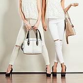 Two ladies holding handbags.