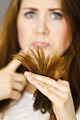 Worried woman looking at her dry hair ends