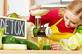 Woman in kitchen making vegetable smoothie juice