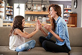 Mother And Daughter Sitting On Sofa Playing Clapping Game