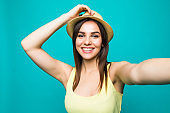 Young woman taking a selfie on a color background