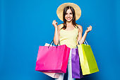 Portrait of the beautiful young woman with shopping bags on the blue background. Black Friday concept.