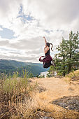 Ecstatic, Young Woman HikerJumping, Fist Pumping, on Mountain Top