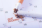Quit Smoking word on calendar sheet with broken cigarette.
