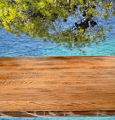 Old pine picnic table, natural  woodgrain texture. Ideal to position products on and place in the foreground of any image.  Selective focus. Very shallow depth of field for soft background. Sea in the background.