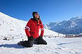 Woman skier enjoying the sun, sunbathing,  at sunny ski resort. Dolomites in Italy. Amateur Winter Sports.