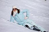 Woman skier enjoying the sun, sunbathing, lying, at sunny ski resort Dolomites in Italy Amateur Winter Sports