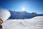 Snowmaking with snow gun Ski slope artificial snowing Ski resort at sunny ski resort Italy Italian Alps Dolomite Amateur Winter Sports