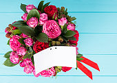 View from above of a blank gift tag with copy space of stylish bouquet of pink and red roses