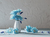 blue flowers in vase on white grunge background