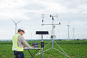 Engineer using tablet computer collect data with meteorological instrument to measure the wind speed, temperature and humidity and solar cell system on corn field background, Smart agriculture technology concept