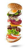 Maxi hamburger with flying ingredients on white background