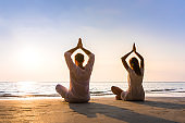 Couple practicing yoga on the beach in morning sunlight, relaxation