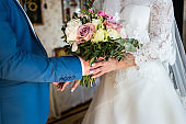 the bride holding a wedding bouquet in the hands of a wedding bouquet and hands closeup, wedding accessories, wedding,loving couple holding wedding bouquet in hands