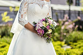 the bride holding a wedding bouquet in the hands of a wedding bouquet and hands closeup, wedding accessories, wedding