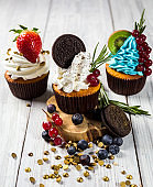 Chocolate cupcakes. Cupcakes. Cupcakes with berries,fruit,strawberries. Top view.colorful cupcake,tasty cake,colorful cream,candies,cupcakes with summer berries on wooden background,close up,dessert concept