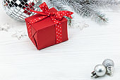 red gift box, fir tree branch and silver christmas decorations on white wood desk