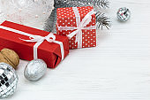 red gift boxes with christmas tree decorations and fir tree branch on white background