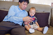 Father and son are using smartphone while spending time together