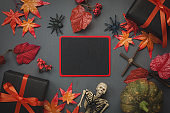 Top view Happy Halloween Holiday background with decoration. Blackboard for free space word.The pumpkin handmade,orange forest leaf,colorful tulip,gift,cross and spiders on wooden background.Flat lay.