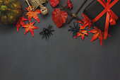 Top view Happy Halloween Holiday background with decoration.The pumpkin handmade,orange forest leaf,skeleton,black gift box and spiders on wooden background.copy space.Above view.