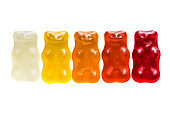 Multi colored gummy bears candy in a row arrangement close-up studio shot