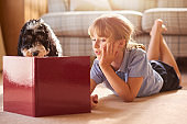 little girl reading a book to her dog