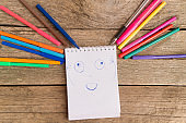 Open white notepad with colorful felt-tip pens and ball pens with drawing glad face on the wooden table.