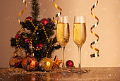 Glasses of champagne on Christmas background with flying snow